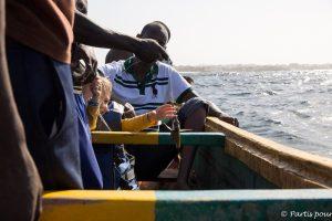 Séance de pêche en pirogue traditionnelle avec les pêcheurs de Yoff. Dakar avec un enfant