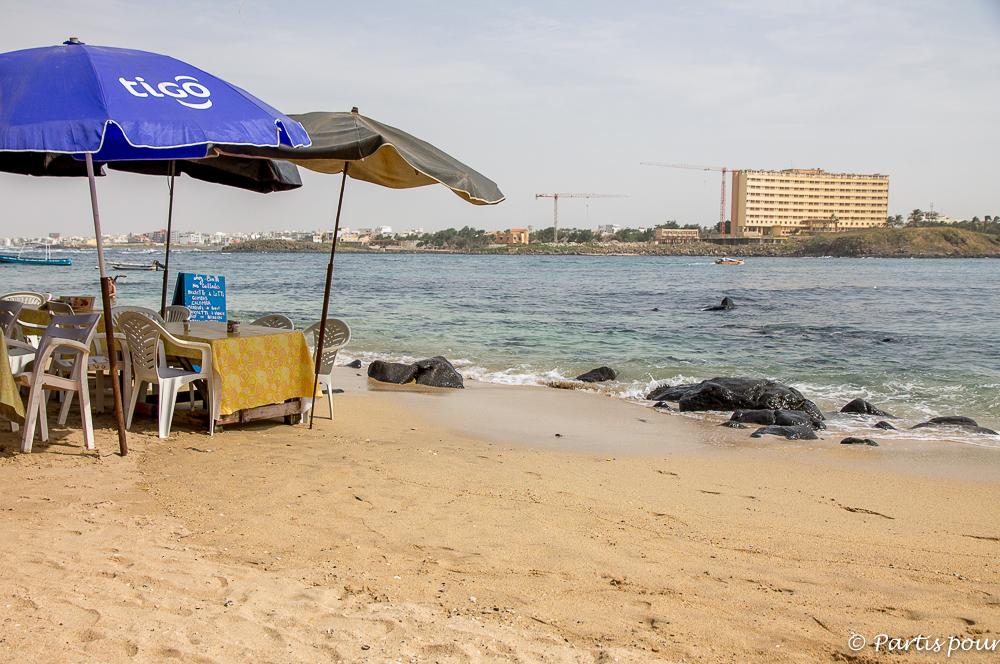 Manger les pieds dans l'eau sur la plage de l'île de NGor. Dakar avec un enfant