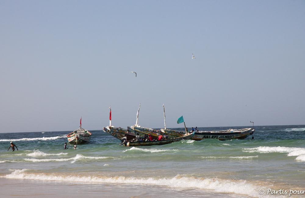 Pirogues de pêche de la plage des pêcheurs de Yoff. Dakar avec un enfant