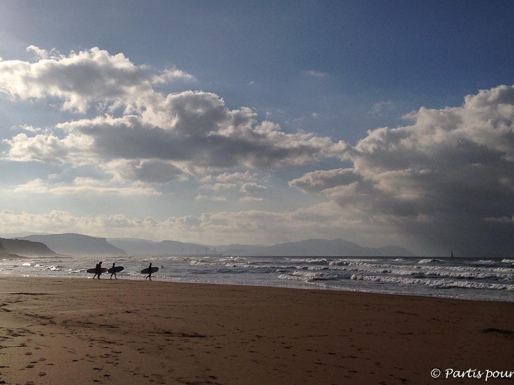 Surfeurs sur la plage de Sopelana au coucher du soleil. Pays-Basque, Espagne